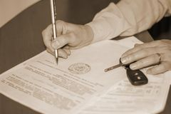 Person signing a document on the sale of the machine stock images