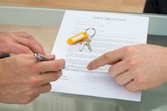 Person signing lease agreement. Close-up Of A Person Signing Lease Agreement Stock Image