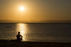 Person in silhouette at beach. Watching sun go down Royalty Free Stock Images