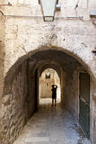 Person silhouette - gate in Dubrovnik. View on narrow alley in Dubrovnik. Person silhouette stony gate Royalty Free Stock Photography