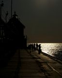 Person in Silhouette on Pier Fishing. People walking and fishing off a pier in silhouette during the sunset Stock Photography