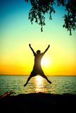 Person Silhouette at Sunset. Vignetting Photo of Happy Person jump on the Sunset Background at Seaside Stock Photography