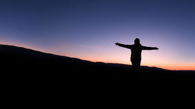 Person silhouetted at sunset. In the mountains Stock Photos