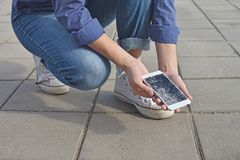 Person holding Broken Smart Phone with a cracked screen. Person sit and holding Broken Smart Phone with a cracked screen stock photo