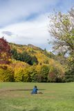 Person Sits On Grass In inidentificable Front Of un contexto colorido fotos de archivo