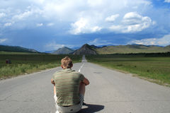 Person sits on road. Man sits in the middle of road of the leader to mountains Royalty Free Stock Images