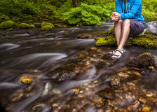 Person sits on the stone covered with moss in the center of rapid flow of the river, holding his feet in clear water Stock Photography