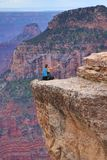 Person taking dangerous selfie in Grand Canyon, Arizona, USA. Person sits on the very edge of the cliff above the abyss of Grand Canyon and tries to take selfie royalty free stock photo