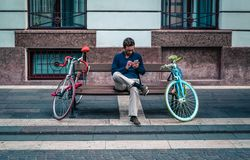 Person Sitting on Bench Between Two Road Bikes Royalty Free Stock Photography