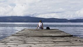Person Sitting on Brown Wooden Dock Under Cloudy Blue Sky Stock Photo