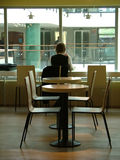 Person sitting in the cafeteria. Person sitting alone in the cafeteria Royalty Free Stock Photos