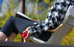 Person sitting in Chair inside rural Garden reading Book holding Pomegranate Stock Photography