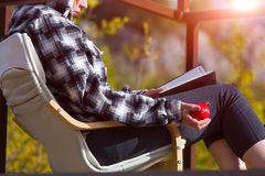 Person sitting in Chair inside rural Garden reading Book holding Pomegranate Royalty Free Stock Photo