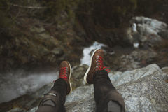Person Sitting on Cliff Wearing Brown Sneakers With Red Lace Royalty Free Stock Image