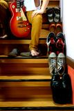 Person sitting beside Different shoes on a staircase and holding a guitar Royalty Free Stock Images