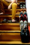 Person sitting beside Different shoes on a staircase Stock Photos