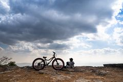 A person sitting down beside a bicycle on rocky mountain. Looking out at scenic natural view and beautiful blue sky stock photo