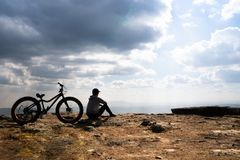 A person sitting down beside a bicycle on rocky mountain. Looking out at scenic natural view and beautiful blue sky royalty free stock image