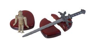 Person Sitting em um coração quebrado com uma espada Imagem de Stock