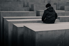 Person sitting on holocaust monument