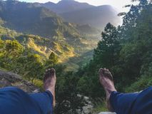 A person sitting and legs is showing and a nature mountain view before him stock photo