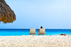 Person Sitting On Lounge Chair At The Beach Stock Image