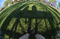 Person sitting at park bench with shadows Royalty Free Stock Photos