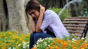 Person Sitting In Park joven preocupante Foto de archivo libre de regalías