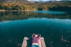 Person sitting on peer by the lake royalty free stock photos