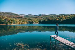 Person sitting on peer by the lake stock images