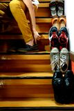 Person sitting and putting on shoes beside Different shoes on a staircase Royalty Free Stock Images