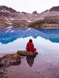 Person Sitting On Rock By The Lake Stock Photo