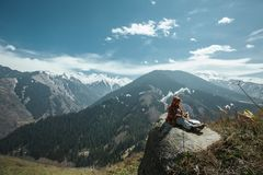 Person Sitting on Rock Near Cliff Stock Image