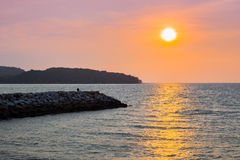 Person sitting on rocks watching sunset on Langkawi island. In Malaysia with an orange sky Stock Photos