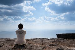 A person sitting on rocky mountain looking out at scenic natural view. And beautiful blue sky royalty free stock photo