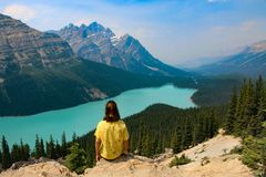 Person Sitting on Rocky Mountain Near Body of Water Stock Images