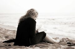 Person Sitting on the Seashore While Reading a Book Royalty Free Stock Image