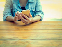 Person sitting at table and using mobilephone Royalty Free Stock Images