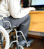 Person sitting in a wheelchair at a desk with computer Stock Photography