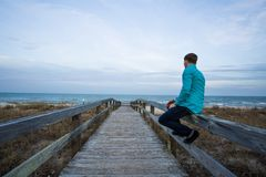 Person Sitting on a Wooden Walkway Royalty Free Stock Photo