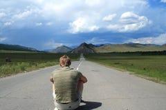 Person sitzt auf Straße lizenzfreie stockbilder