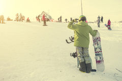 Person in ski suit with snowboards looking on the hill Royalty Free Stock Photo
