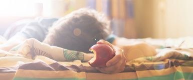 Person sleeping and lying in the bed abd bite and eat fresh apple f stock photography