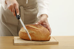 Person slicing a loaf of bread Royalty Free Stock Images