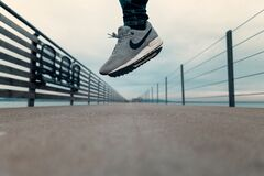 Person with sneakers drops onto bridge Stock Photos