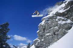 Person On Snowboard Jumping Midair. Low angle view of a person on snowboard jumping midair over cliff stock photos