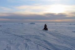 The person on a snowmobile at sunset Royalty Free Stock Photos