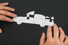 Person solving car jigsaw puzzle Stock Photo