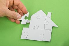 Person solving house jigsaw puzzle Royalty Free Stock Image
