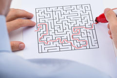Person Solving Maze Puzzle. Close-up Of Person With Red Marker Pen Solving Maze Puzzle stock images